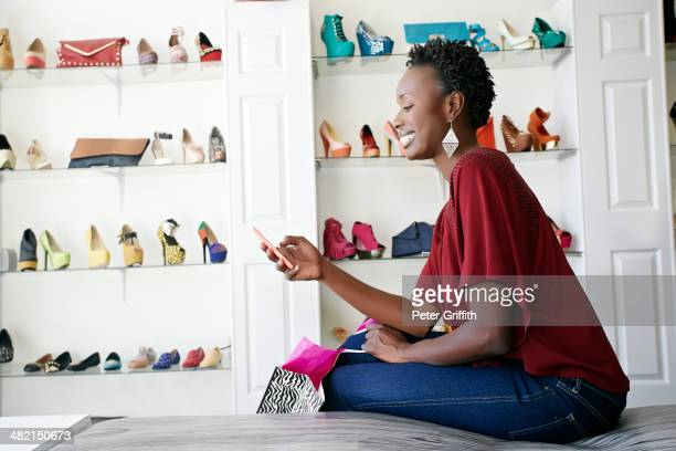 african american woman using cell phone in shoe store - chaussures noires photos et images de collection