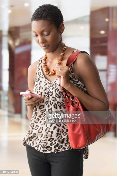 African American woman using cell phone in shopping mall