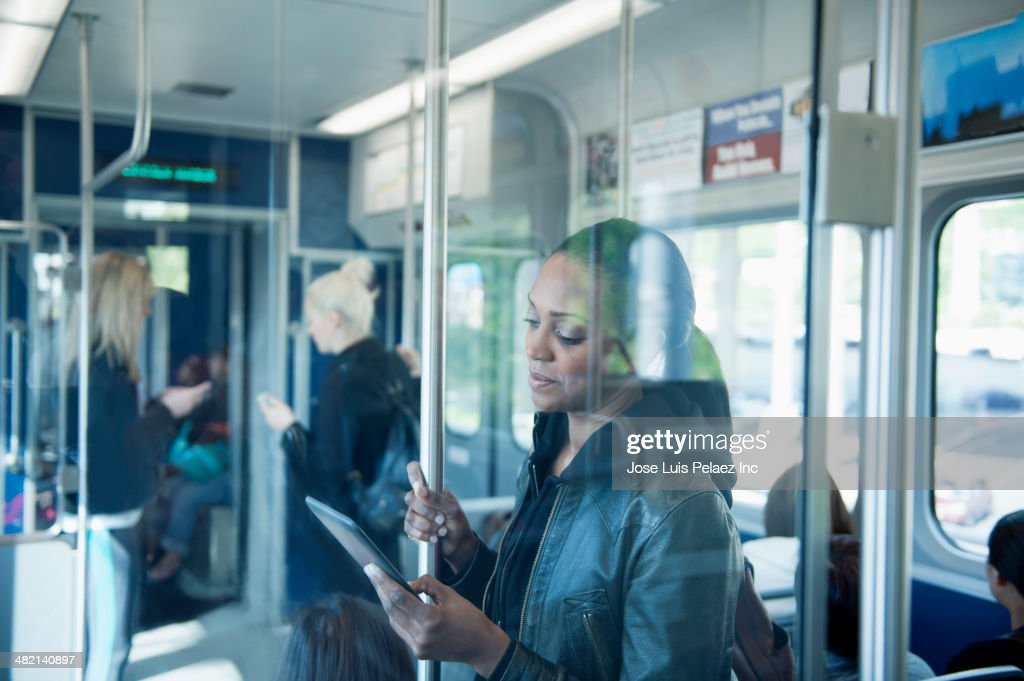 African American woman using digital tablet on train : Stock Photo