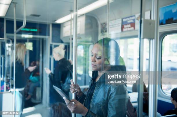 african american woman using digital tablet on train - 通勤電車 ストックフォトと画像