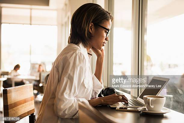 African American woman using laptop in cafe