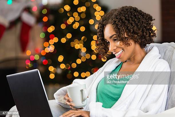 African American woman using laptop to Christmas shop from home