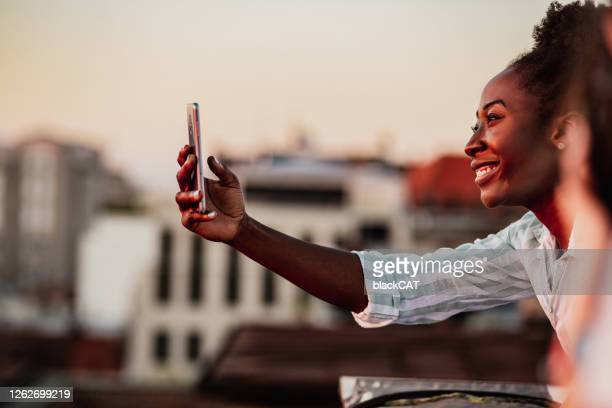 african american woman using mobile phone and relaxing - active lifestyle stock pictures, royalty-free photos & images