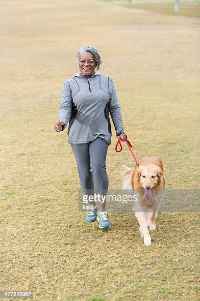 African American woman walking dog