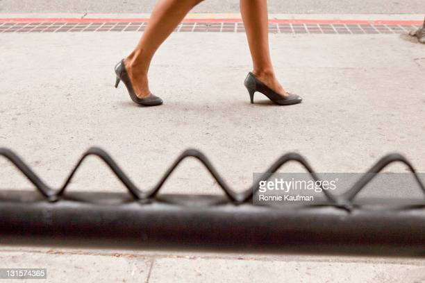African American woman walking in high heels on sidewalk