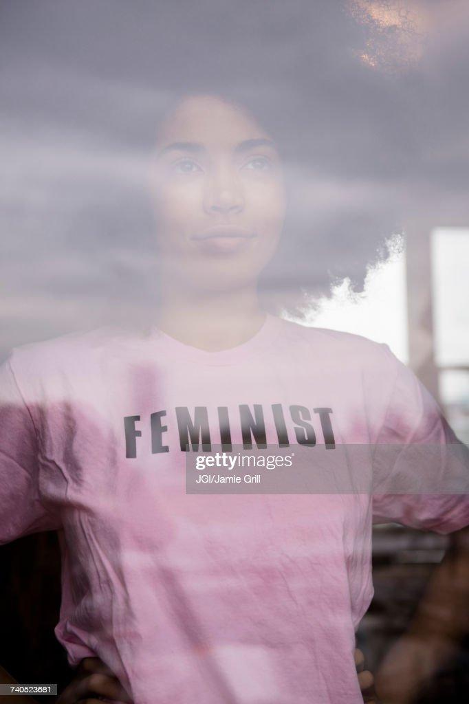 African American woman wearing feminist t-shirt behind window : Stock Photo