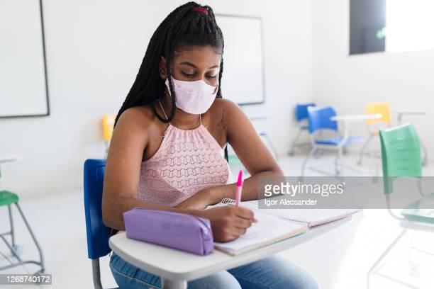 afroamerikanische frau trägt maske im klassenzimmer - einzelveranstaltung stock-fotos und bilder