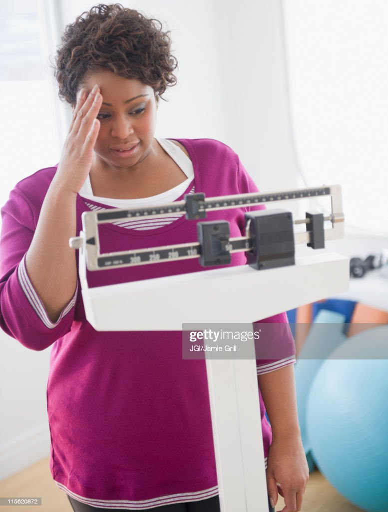 African American woman weighing herself : Stock Photo