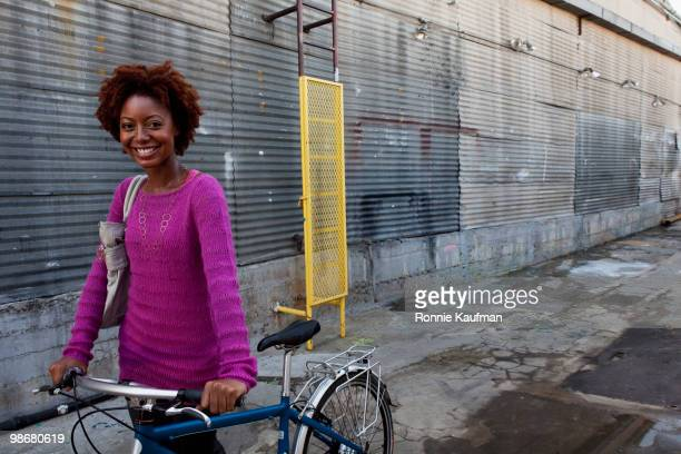 african american woman with bicycle in urban alley - black alley stock photos and pictures
