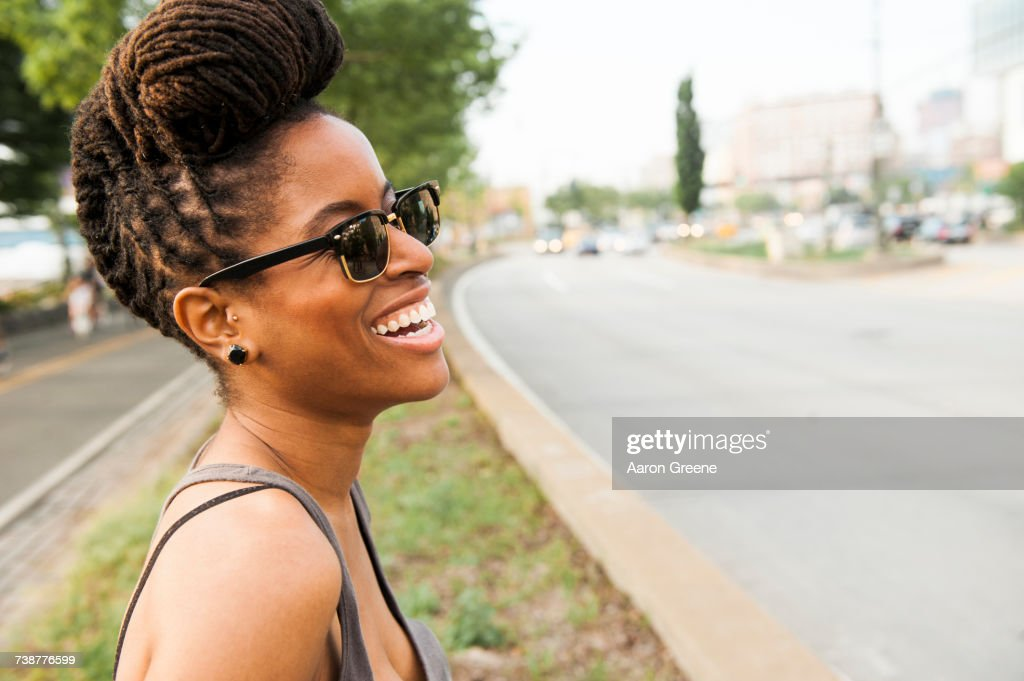 African American woman with braids laughing near street : Stock Photo