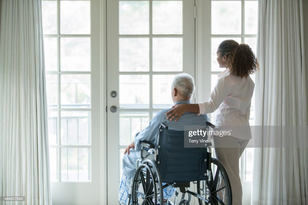 African American woman with Senior man in wheelchair : Stock Photo