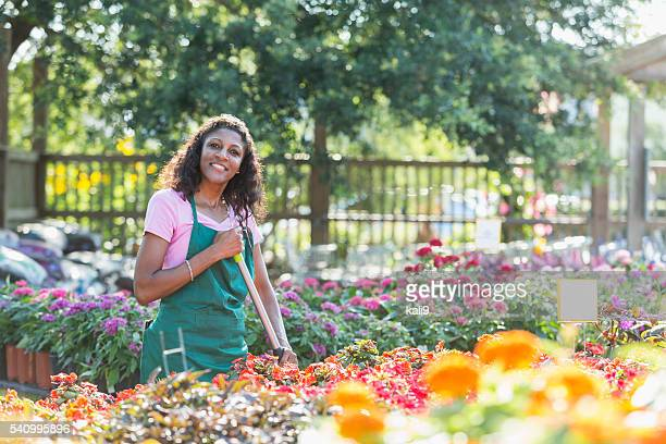 african american woman working in plant nursery - sweeping stock pictures, royalty-free photos & images