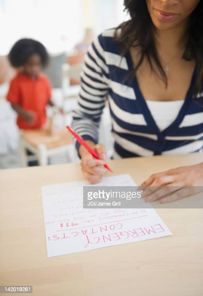 african american woman writing out contact phone numbers - contact list stock photos and pictures
