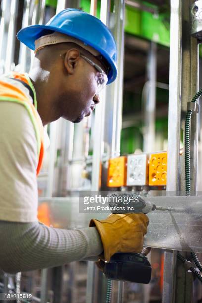 African American worker drilling metal on site
