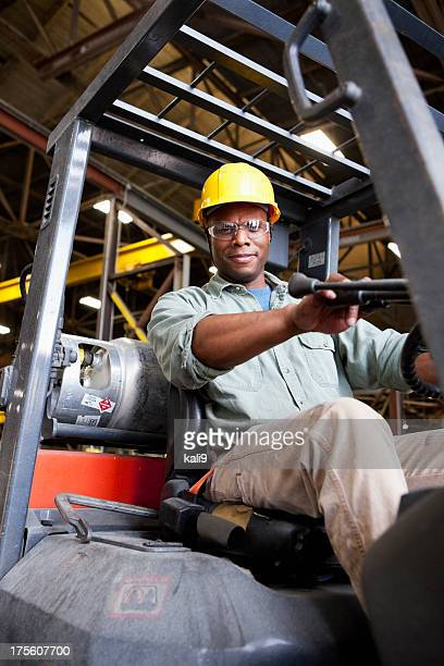 African American worker driving forklift