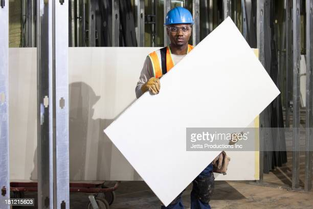 African American worker holding blank piece of two-by-four.