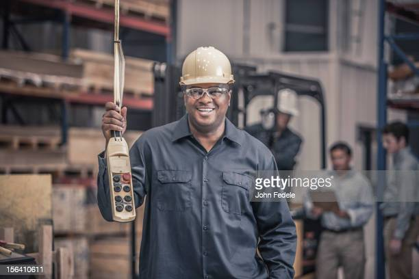 African American worker holding control panel in factory