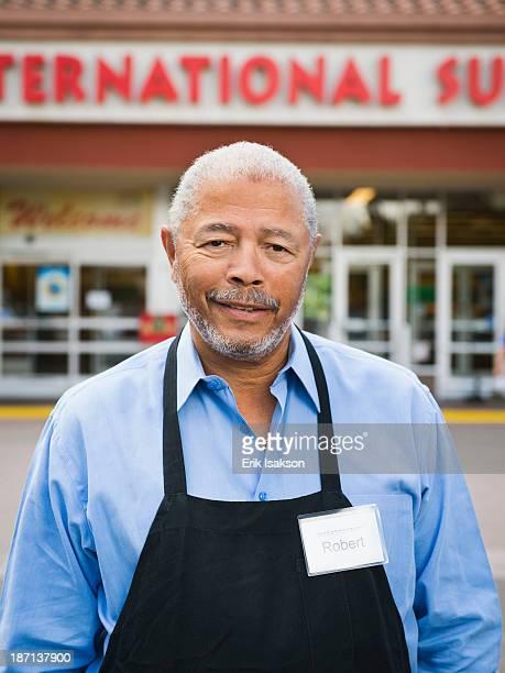 african american worker smiling outside grocery store - fachada supermercado imagens e fotografias de stock