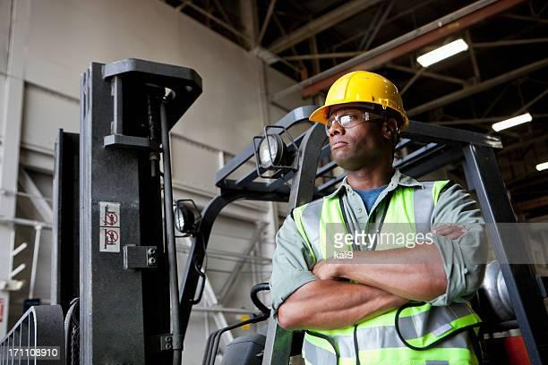 Afrikanische amerikanischer Arbeiter stehend am Gabelstapler