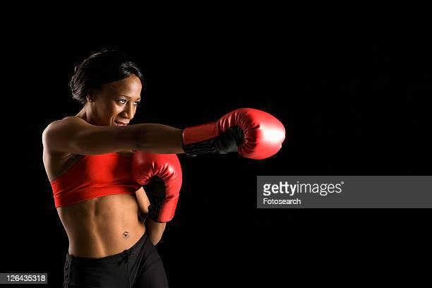 african american young adult woman wearing boxing gloves throwing punch. - belly punch stock pictures, royalty-free photos & images