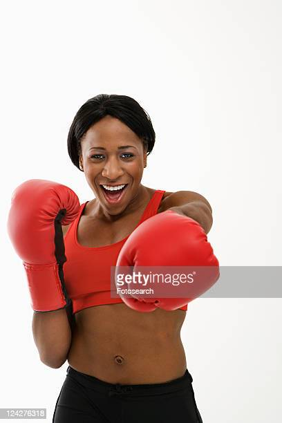 african american young adult woman wearing boxing goves throwing playful punch at viewer. - belly punch stock pictures, royalty-free photos & images