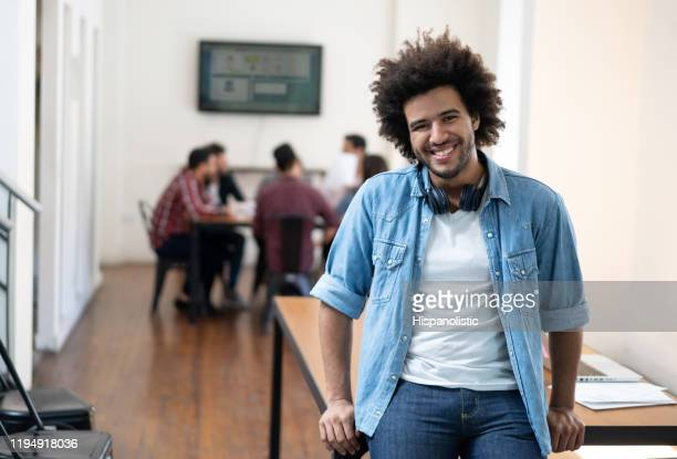 african american young man at a coworking office wearing headphones on neck smiling at camera cheerfully - incidental people stock pictures, royalty-free photos & images