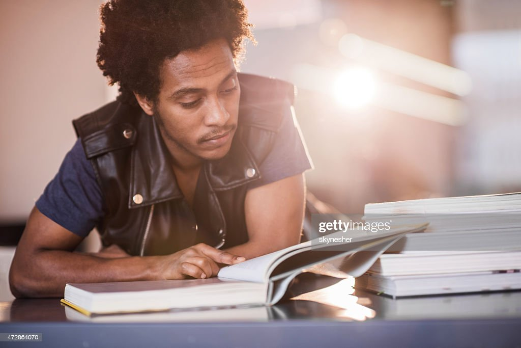 African American young man reading a book and studying. : Stock Photo