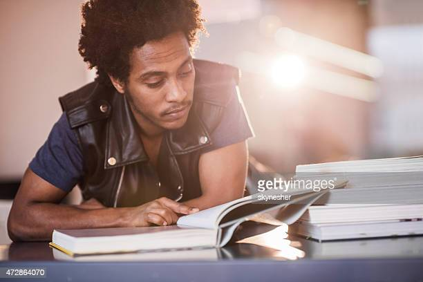 African American young man reading a book and studying.