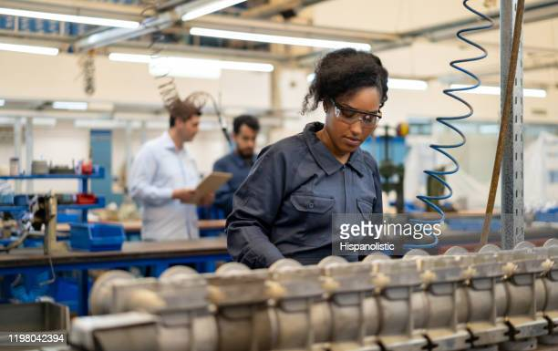 african american young woman working at an assembly production of water pumps at a factory - manufacturing stock pictures, royalty-free photos & images