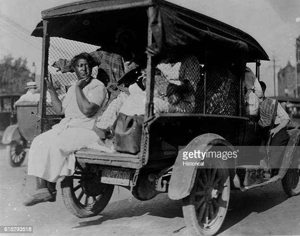 An AfricanAmerican woman sits in the back of a truck her legs hanging over the back Several other people are in the back of the truck also hidden by...