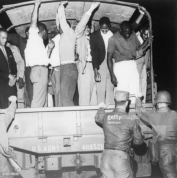 African Americans hang on to the overhead bar of this US army truck to steady themselves as they head for their homes Alabama governor John Patterson...