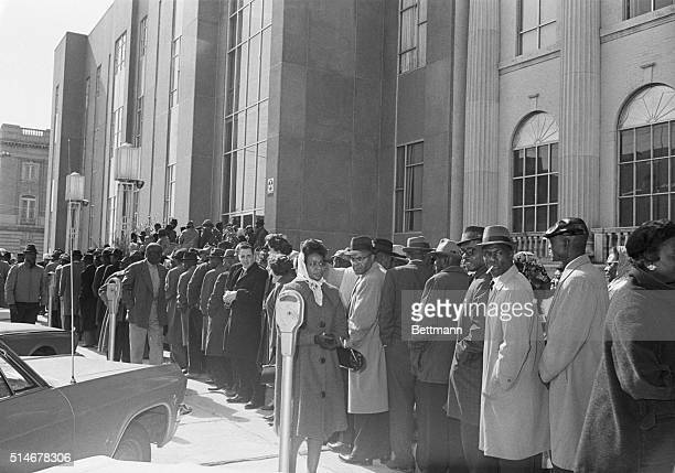 African Americans led by Reverend Martin Luther King Jr line up in front of the Dallas County Courthouse in Selma Alabama to register to vote