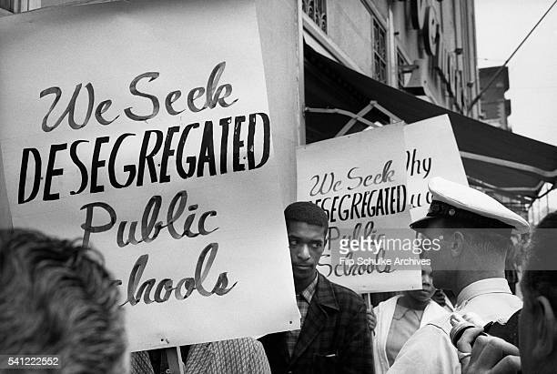 African Americans picket the sidewalks of Birmingham Alabama for desegregated schools A policeman confronts them for the photographers