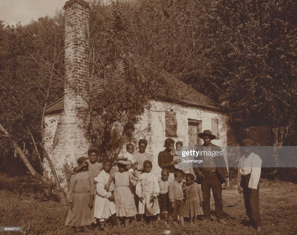 African Americans posed outside former slave quarters at Hermitage Plantation.