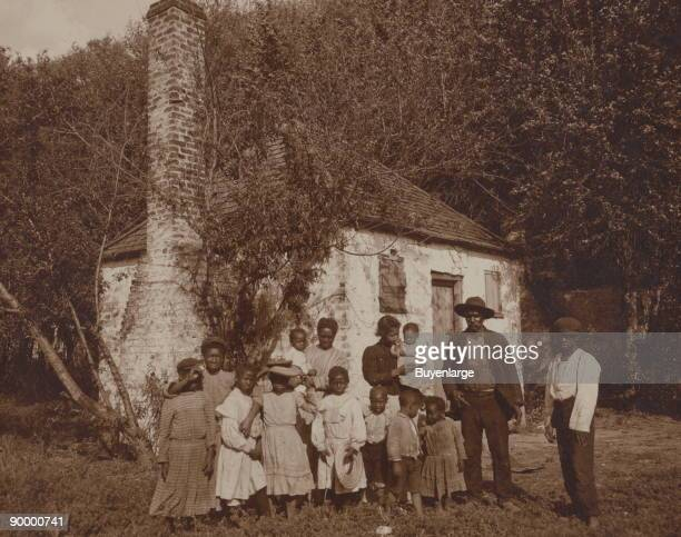 African Americans posed outside former slave quarters at Hermitage Plantation