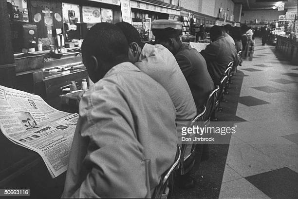 African Americans stage sit down at Woolworth Store's lunch counter in which service was refused to them