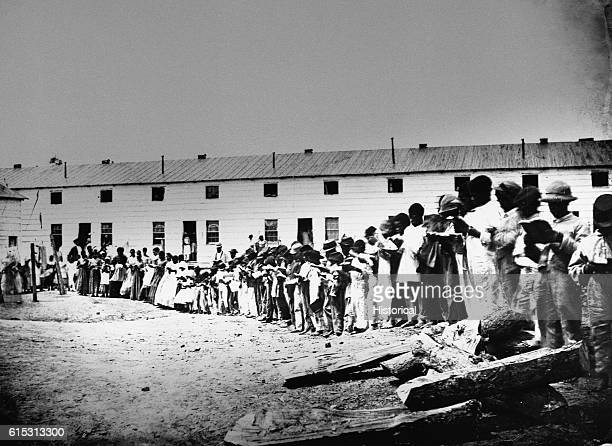 African Americans stand outside a contraband school or Freedman's Village in Arlington Virginia ca 1860s