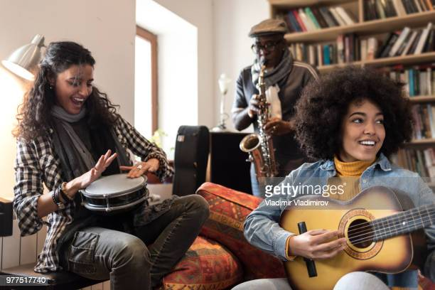 african and caucasian ethnicity band having fun together - tambourine stock photos and pictures