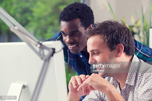 Homme africain et Caucasien travaillant ensemble à la recherche à un ordinateur.