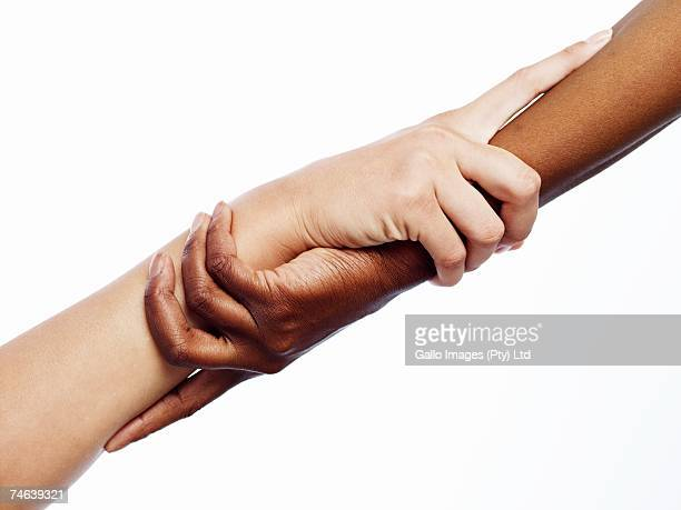 African and Caucasian Woman with their Hands Interlocked