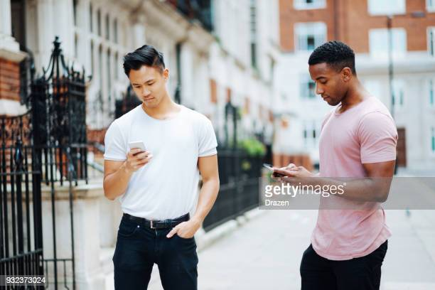 African and Chinese guys using phones on the street