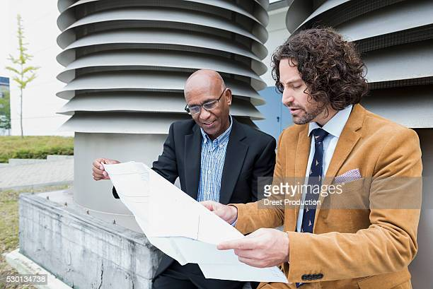African architect client two men blueprint meeting