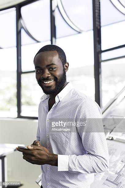 African architect on his phone smiling at the camera.