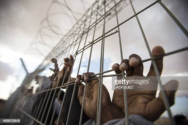 African asylum seekers who entered Israel illegally via Egypt lean at the fence of the Holot detention centre in Israel's southern Negev Desert on...