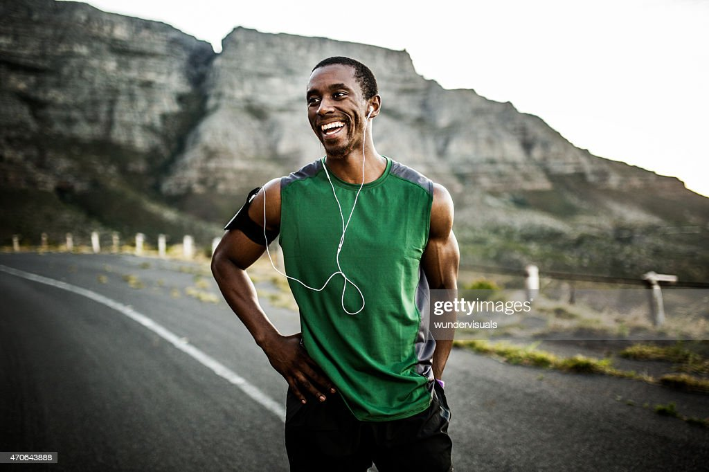 African athlete smiling positively after a good training session : Stock Photo