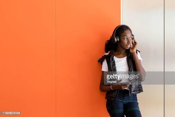 african australian teenage girl listening to music under headphones - hoodie headphones stock pictures, royalty-free photos & images