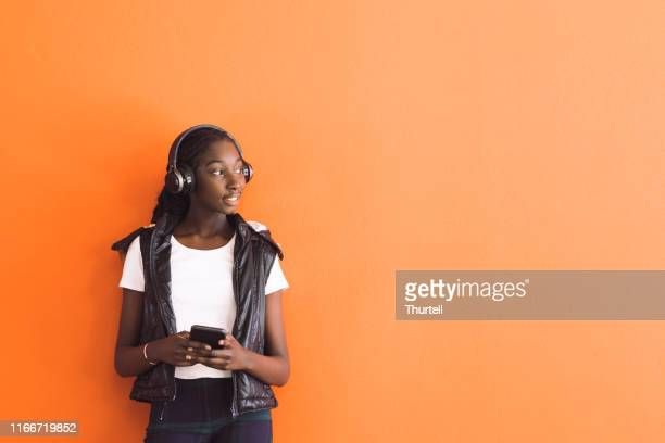 african australian teenage girl listening to music under headphones - orange background stock pictures, royalty-free photos & images