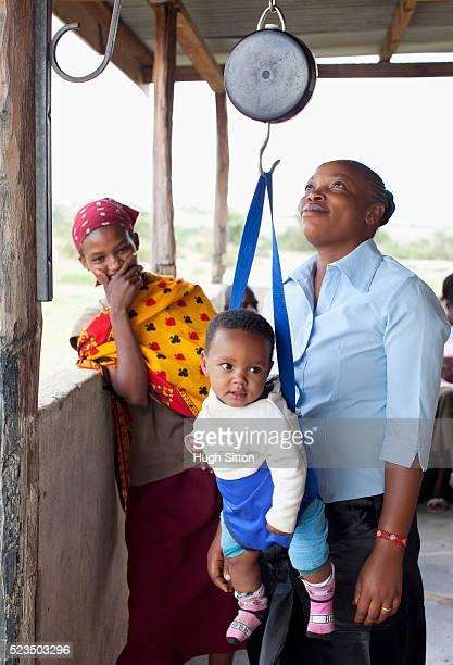african baby boy (6-12 months) hanging on scale in local hospital - hugh sitton stock-fotos und bilder