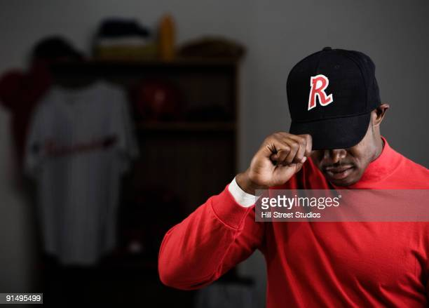 African baseball player adjusting cap in locker room