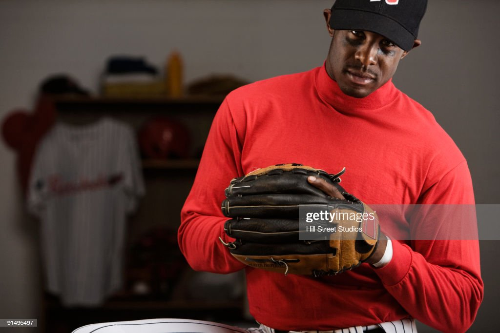 African Baseball Player Holding Glove In Locker Room Stock Photo